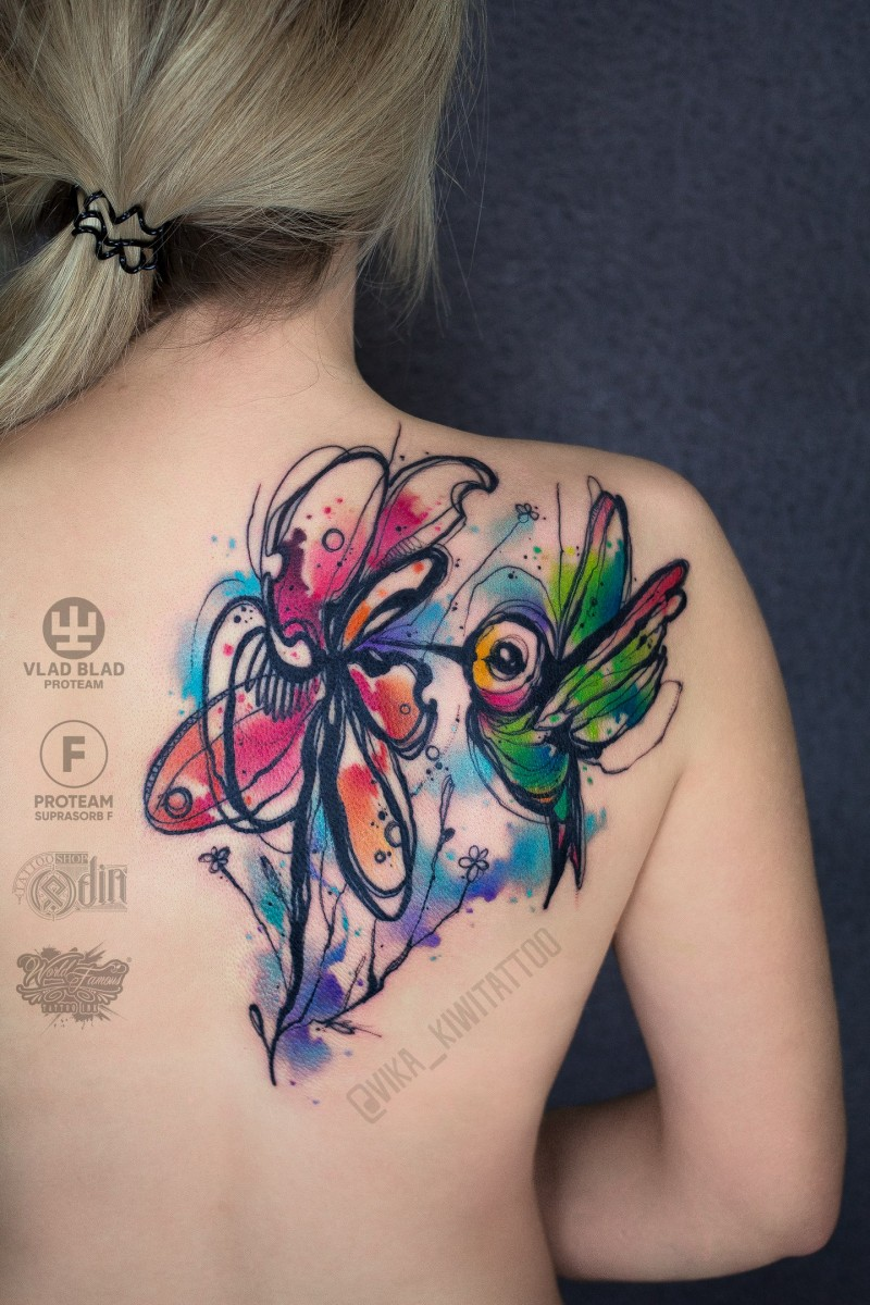Bright watercolor colibri and flower tattoo on womans shoulder
