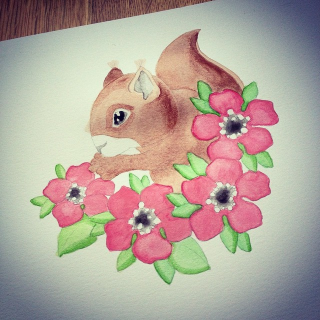 Brown watercolor squirrel baby surrounded with pink flowers tattoo design