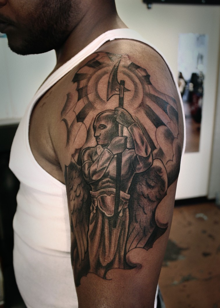 Calm angel warrior with axe tattoo on shoulder