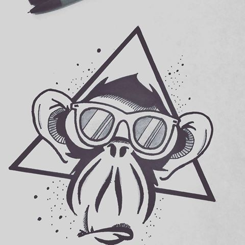Cartoon chimpanzee muzzle in sun glasses in triangle frame tattoo design