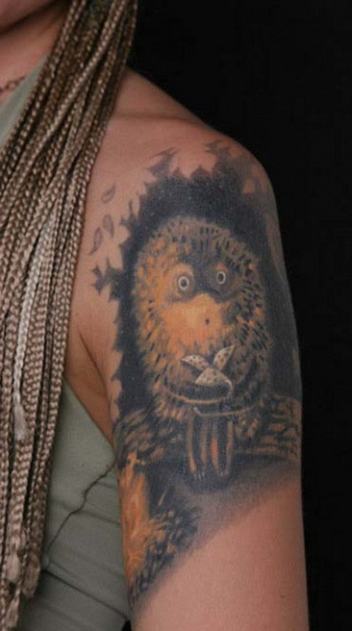Cartoon dark-ink hedgehog sitting on branch tattoo on upper arm