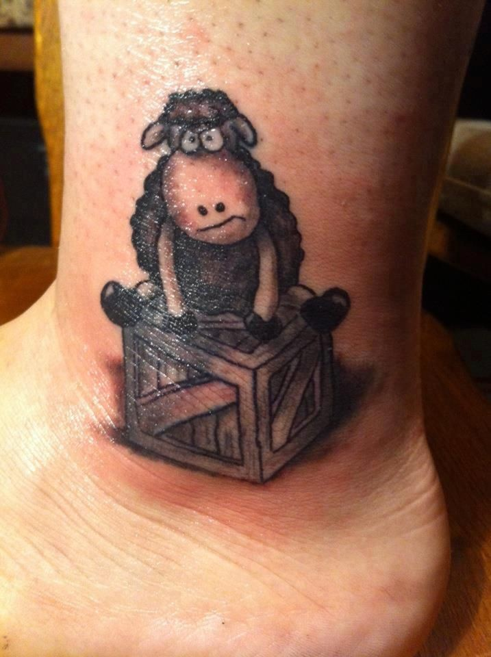 Cartoon sheep sitting on wooden box tattoo on foot