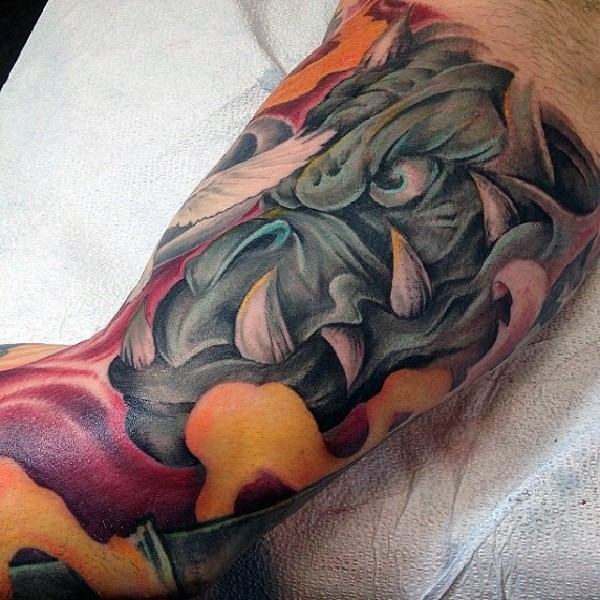 Cartoon style colored gargoyle with big teeth tattoo on biceps