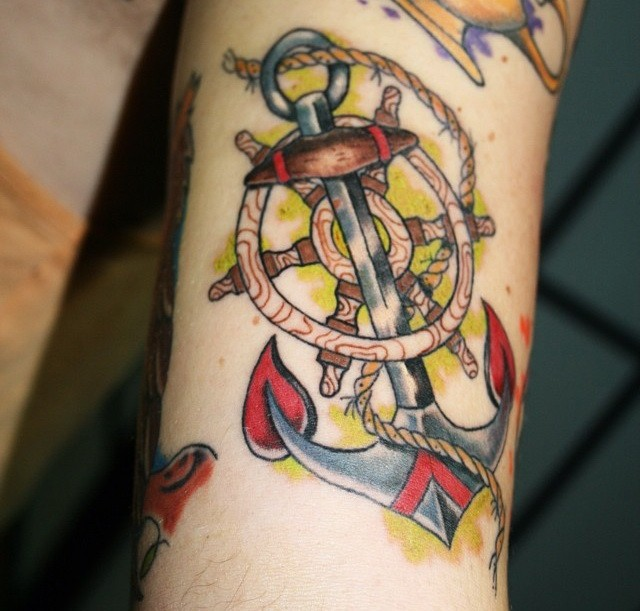 Colored roped anchor with wheel tattoo on forearm