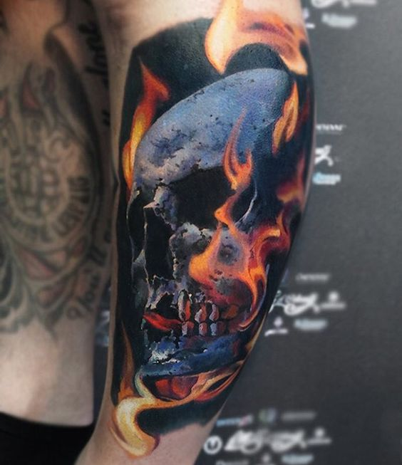 Colored skull with flames tattoo on shoulder by Valentina Ryabova