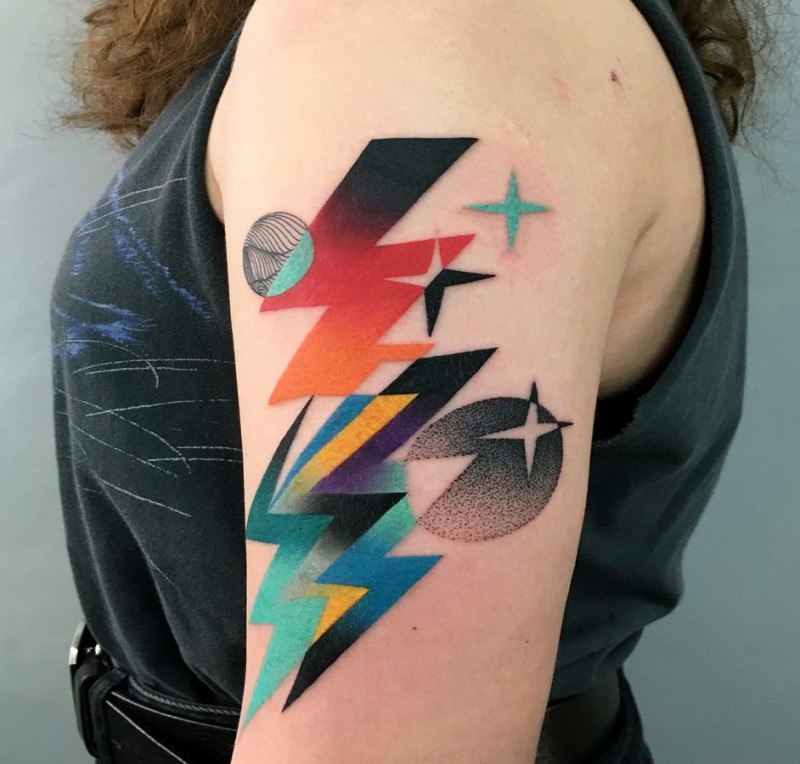 Colorful painted by Mariusz Trubisz upper arm tattoo of planets and lightning