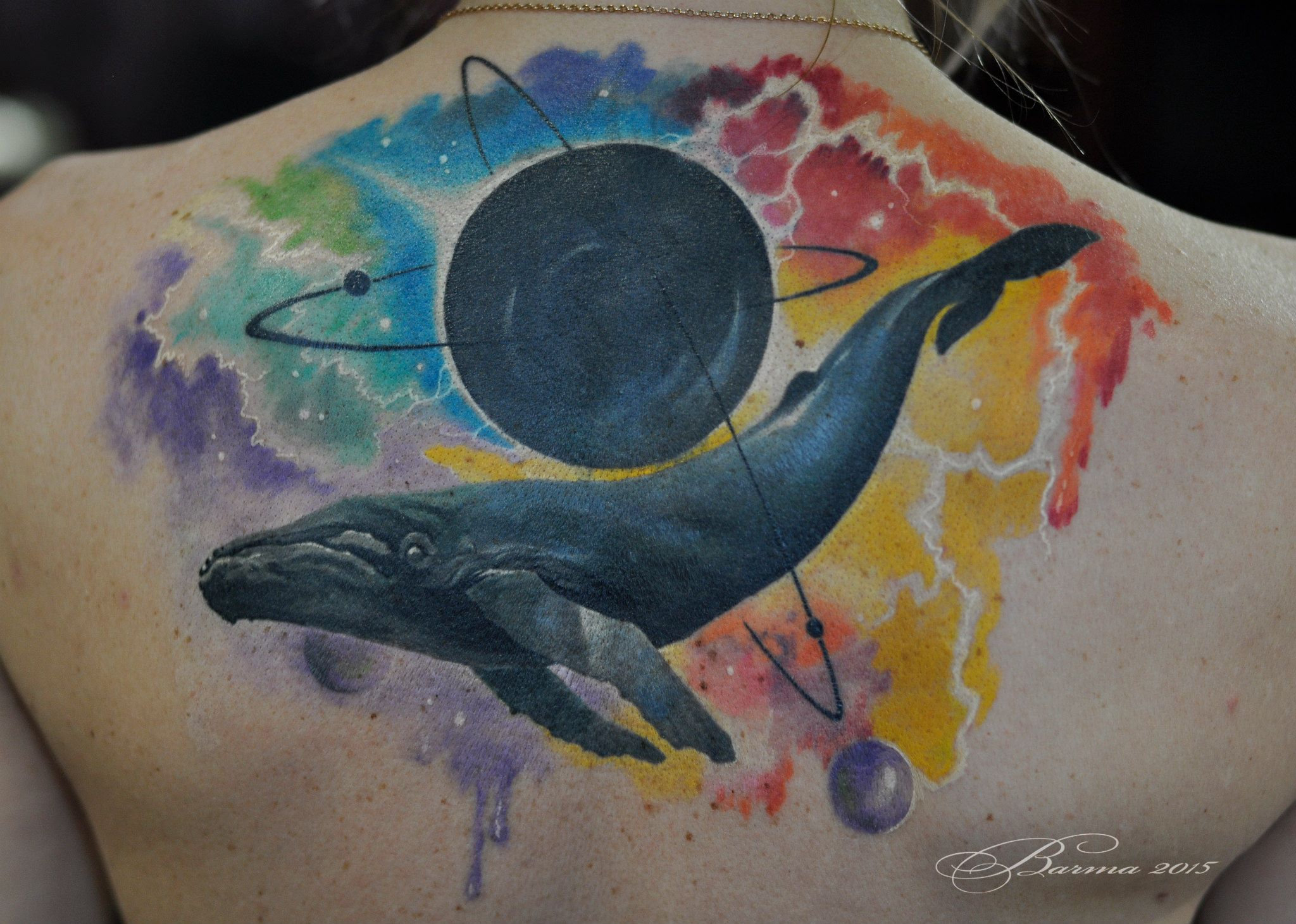 Colorfull whale in space tattoo on upper back