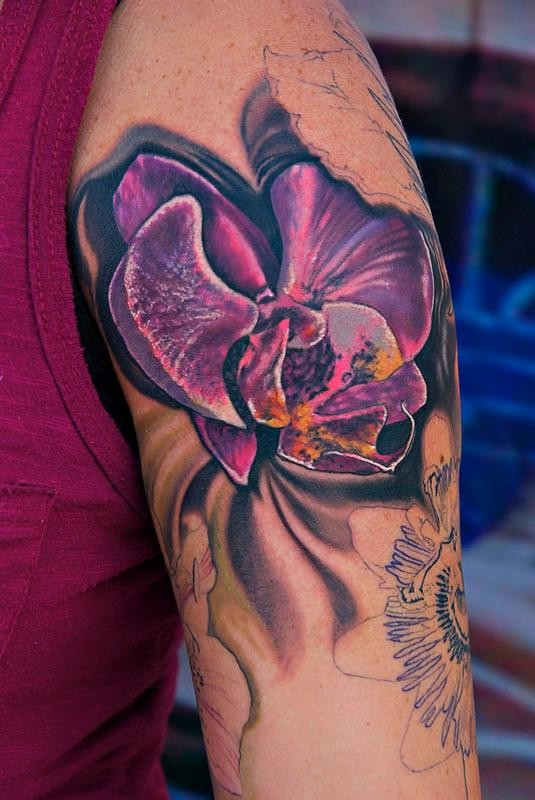 Cool bright violet tropical flower tattoo on upper arm