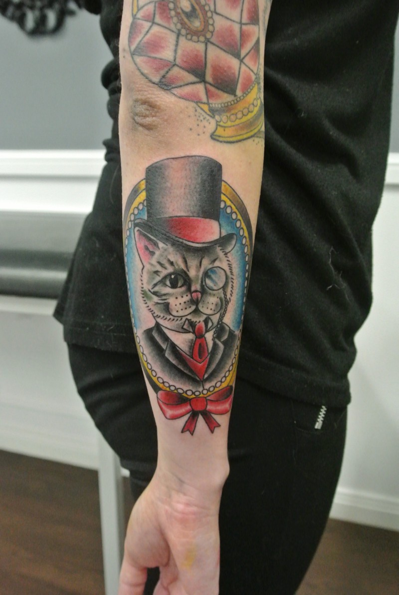 Cool cartoon old school cat in frame tattoo on outer forearm