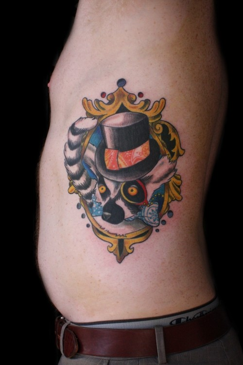 Cool colorful lemur in hat looking out of mirror frame tattoo on side