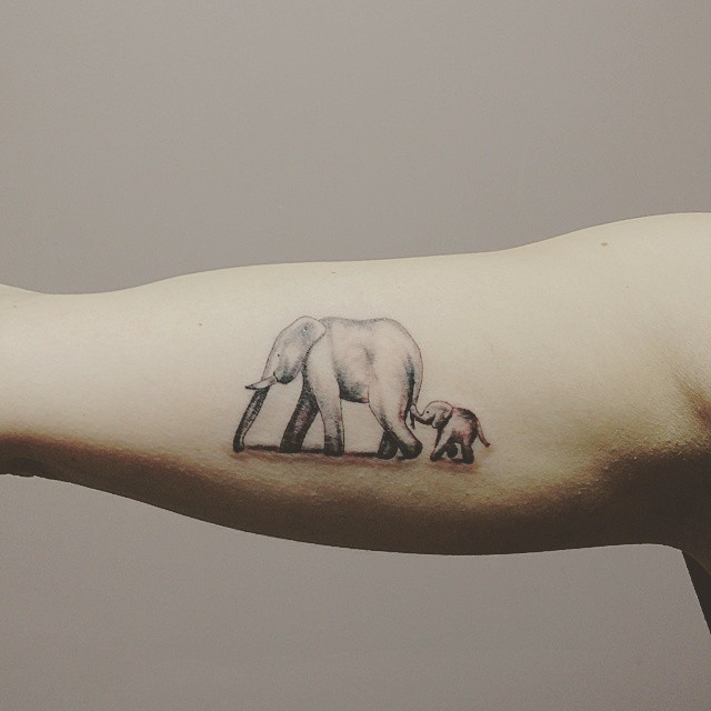 Cool realistic elephant family hangin by tale tattoo on arm