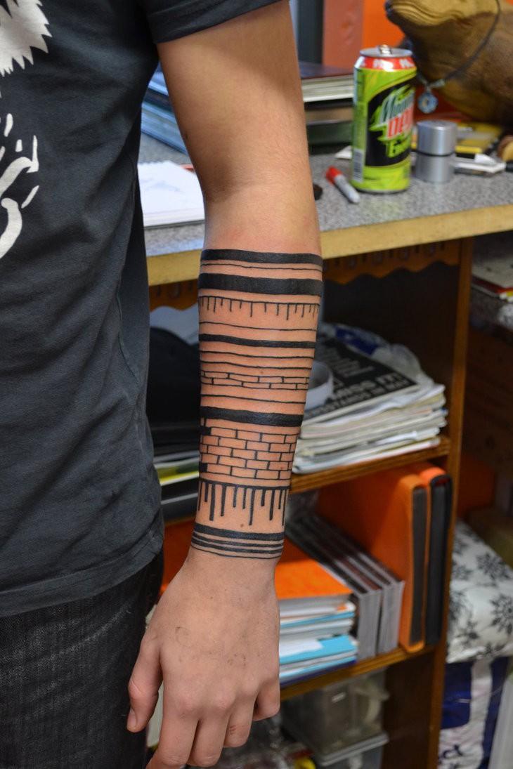 Cool tribal bricked black-ink tattoo sleeve on forearm
