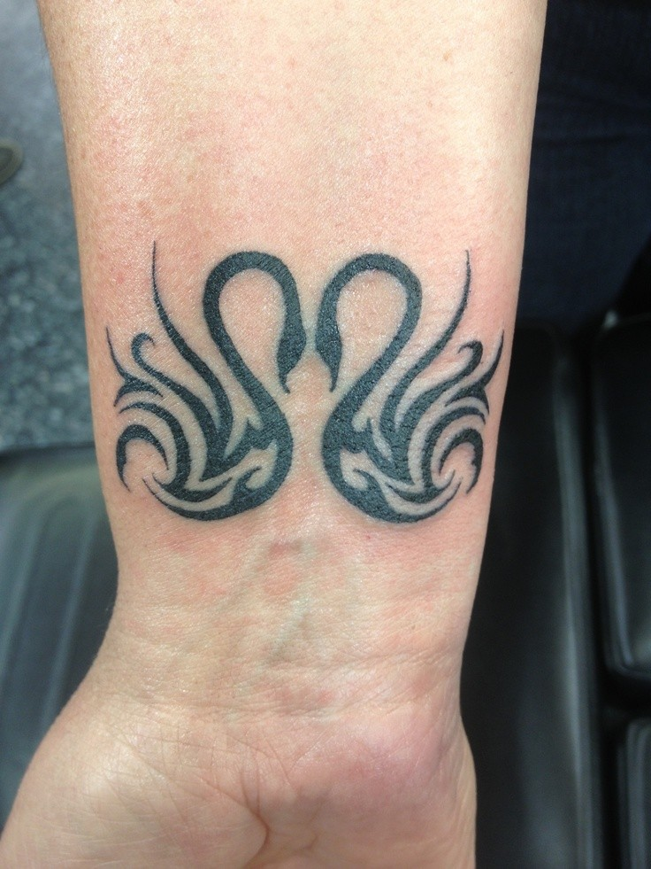 Cool tribal double black-ink swans tattoo on wrist