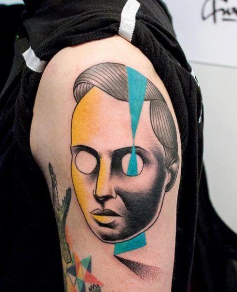 Creepy looking painted by Mariusz Trubisz upper arm tattoo of human like mask