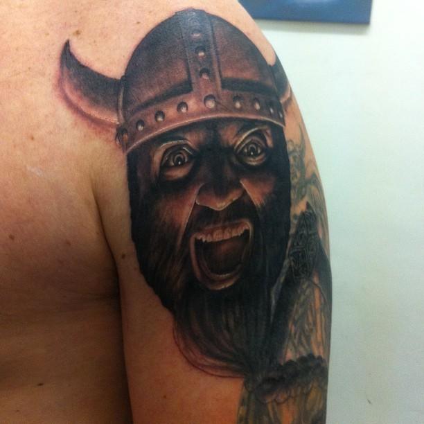Crying Viking head tattoo on shoulder