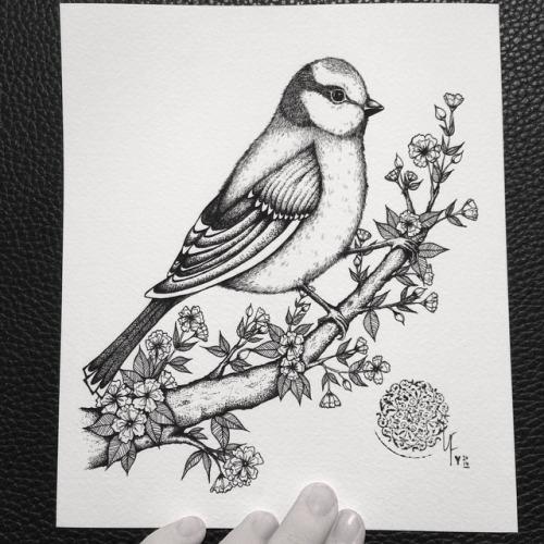 Cute black-and-white bird sitting on blossom branch tattoo design