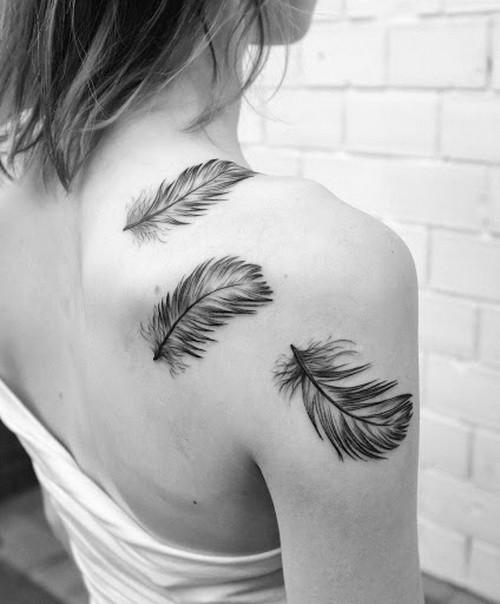 realistiche piume nero e bianco tatuaggio su spalla