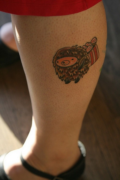 Cute cartoon colorful hedgehog with bag of cakes tattoo on shin