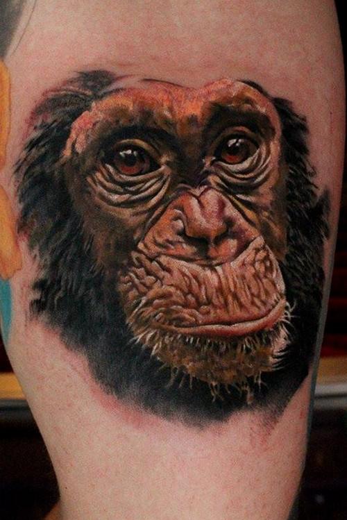 Cute colorful chimpanzee face tattoo on thigh