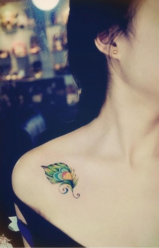 carina piccola piuma colorata tatuaggio su spalla di ragazza