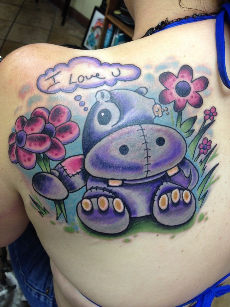 Cute girly cartoon violet hippo with flowers and quote tattoo on back