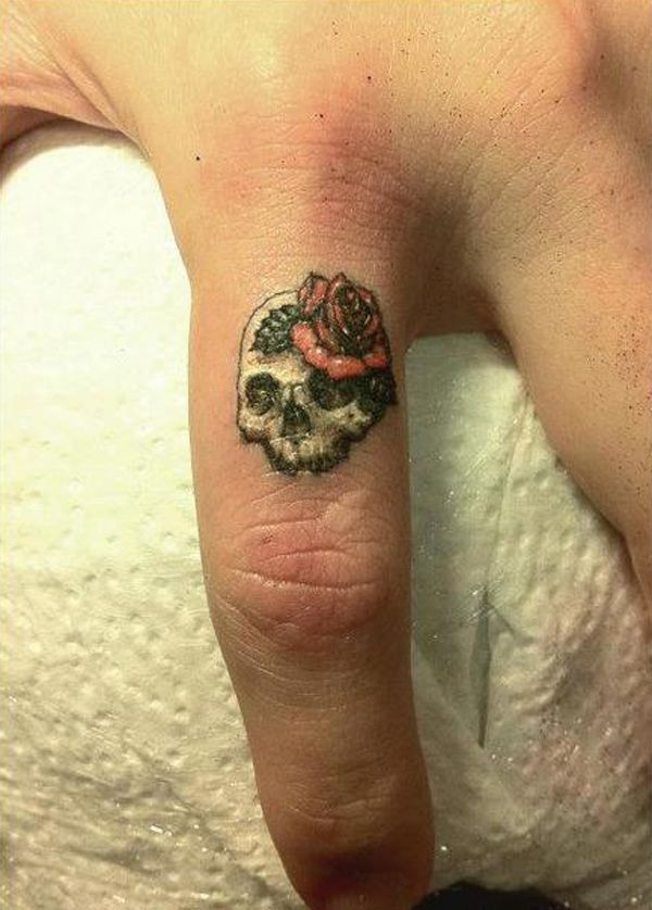 Cute small female scull tattoo on finger