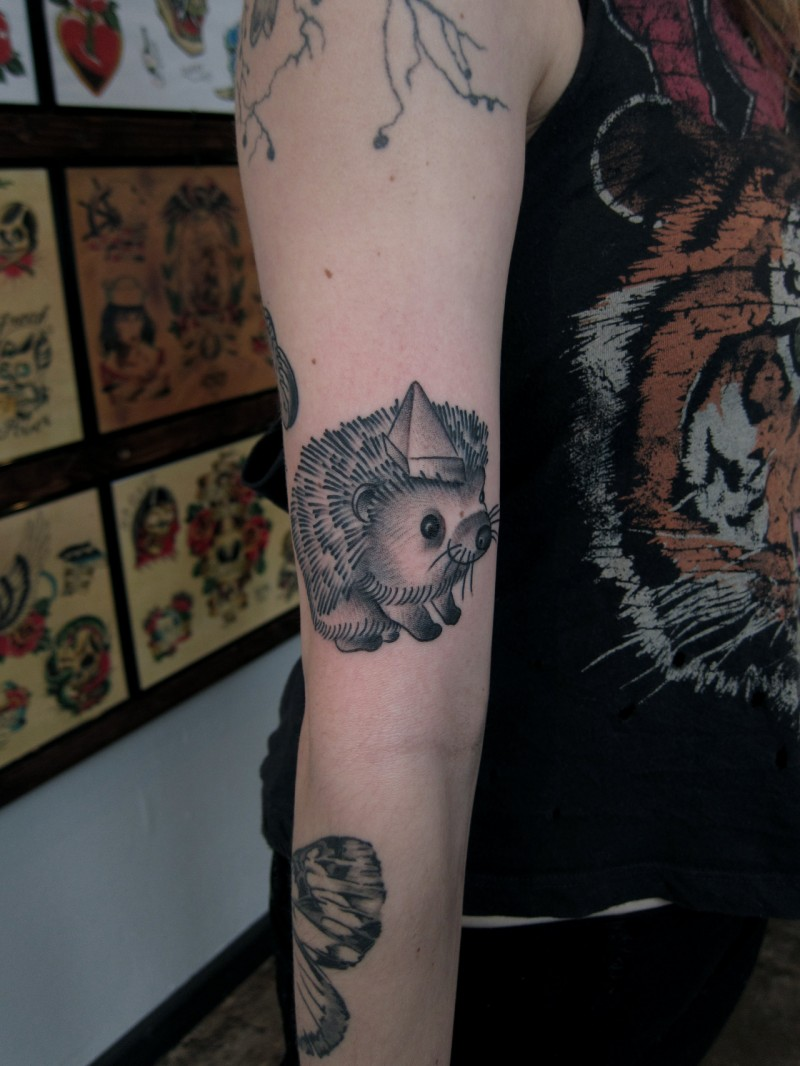 Cute smiling black-and-white hedgehog tattoo on arm