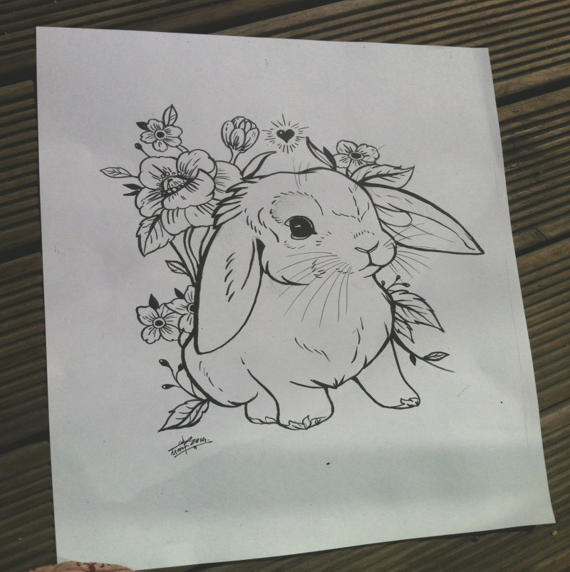 Cute uncolored rabbit surrounded with flowers tattoo design