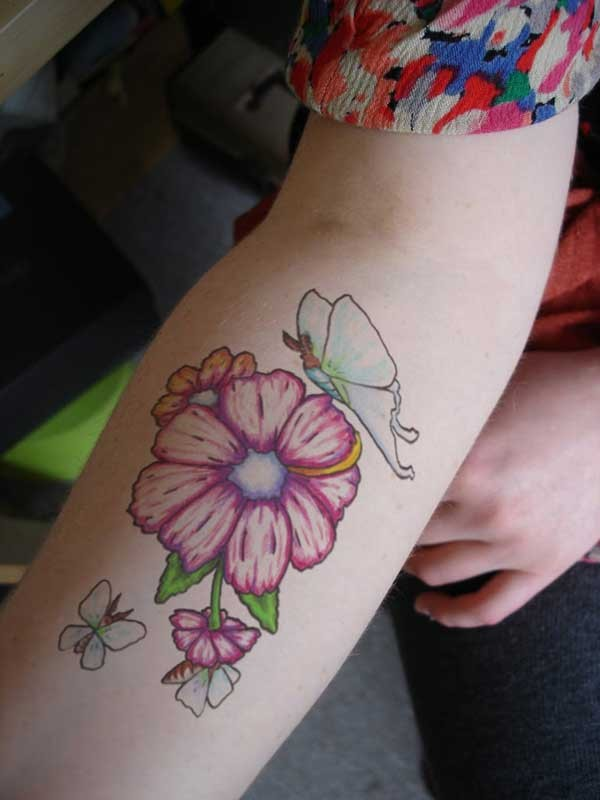 Cute womens pink flower and blue butterfly tatoo on forearm