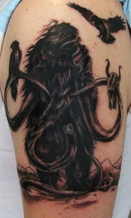 Dark mammoth and ravens tattoo on upper arm