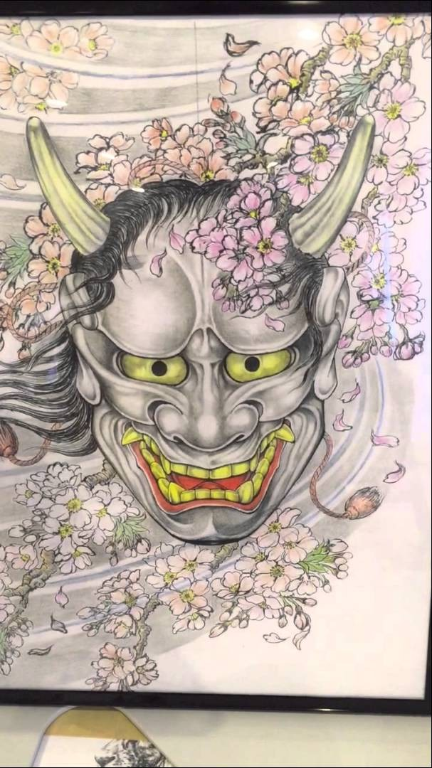Devil with evil grin and rich cherry blossom tattoo design