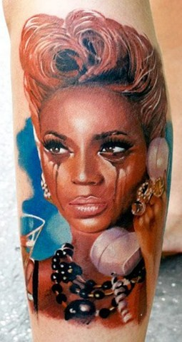 Dramatic colored leg tattoo of crying woman with phone