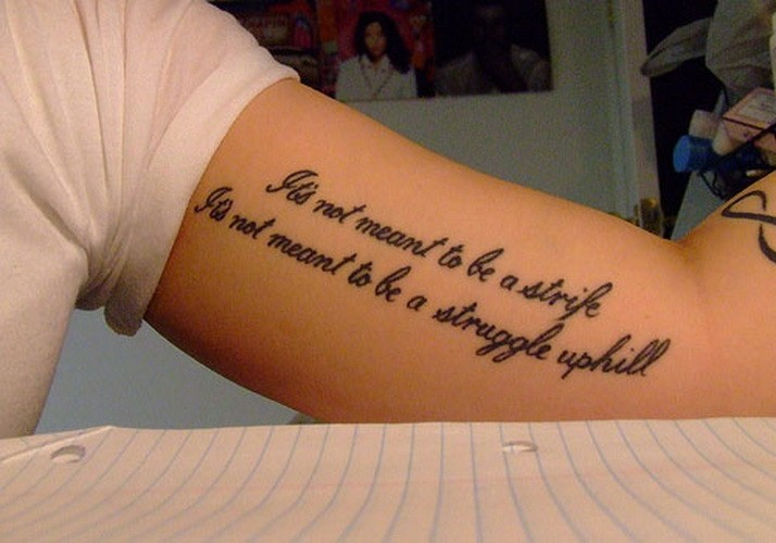 Dreadful black-and-white quote tattoo on arm