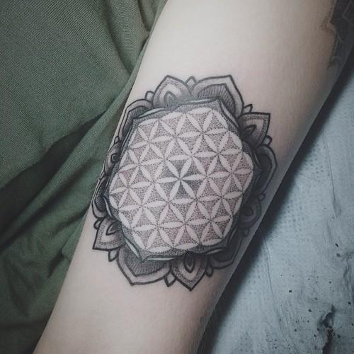 Elegant black-ink flower of life tattoo on arm