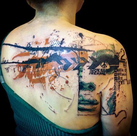 Enormi tatuaggi multicolori sulla parte superiore della schiena e sulle spalle di strani ornamenti con volto femminile