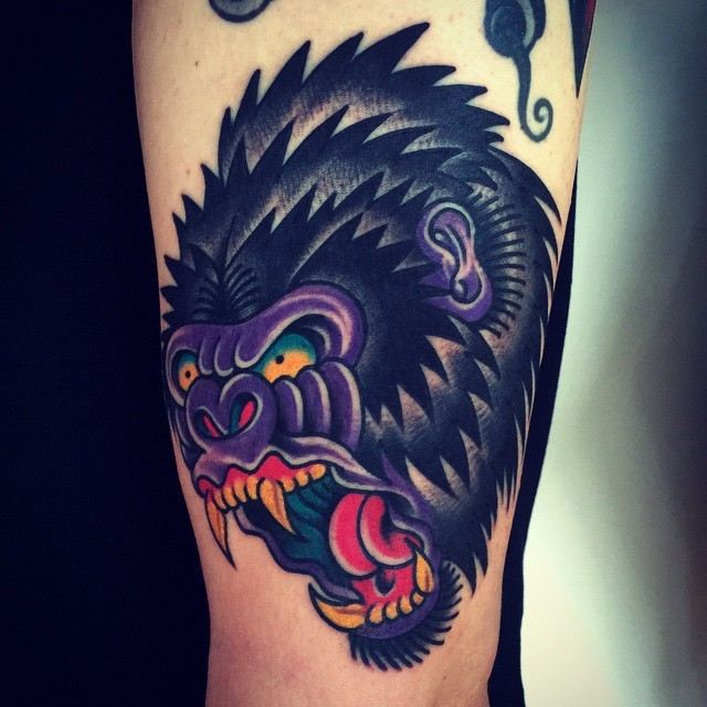 Enraged shaggy color-ink gorilla head tattoo on arm