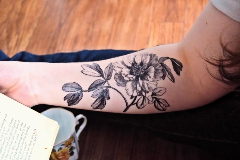 Exiting black-ink vintage flower on stem tattoo on arm