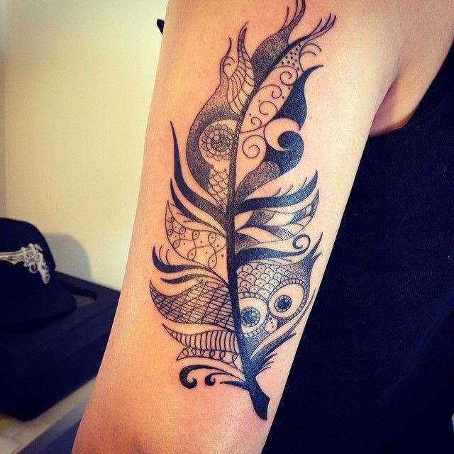Funny black-and-white tribal feather with owl face tattoo on upper arm