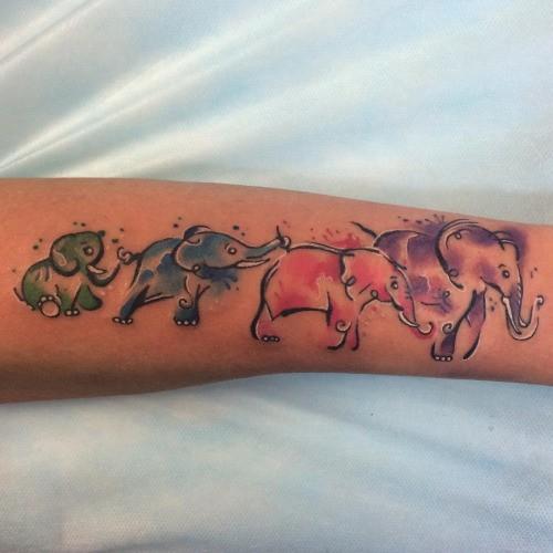 Funny vivid-colored elephant family tattoo on arm