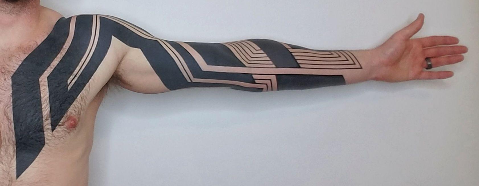 Tatuaggio geometrico blackwork sul braccio di Ben Volt