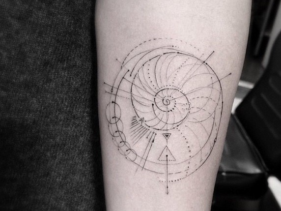 Geometrical style black ink nautilus shaped tattoo on forearm