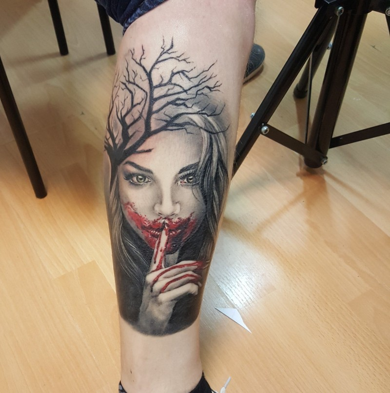 Girl with bloody mouth and dryed tree tattoo on leg