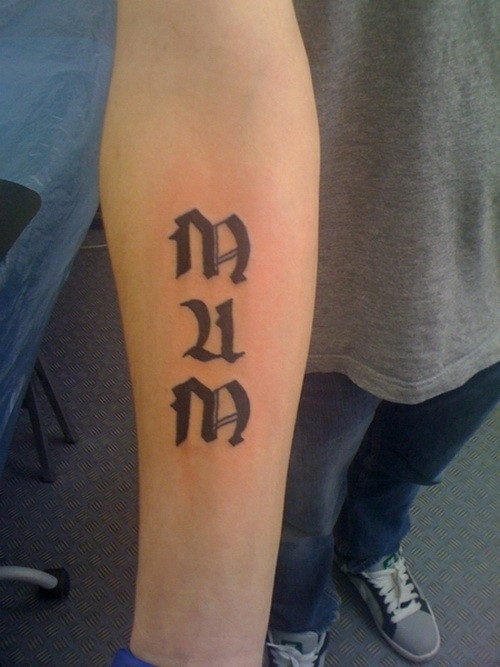 Gothic-lettered mum word tattoo on forearm
