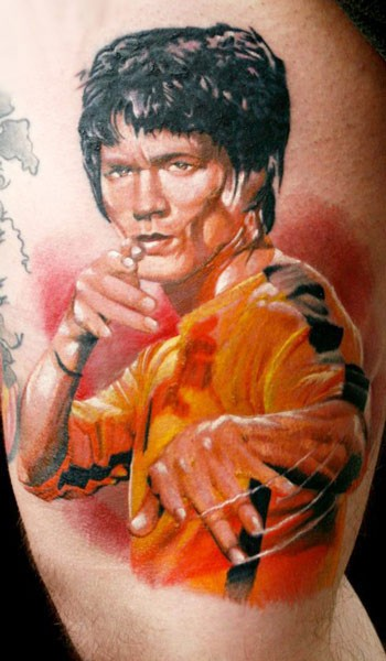 Graffiti style colored Bruce Lee portrait tattoo on thigh