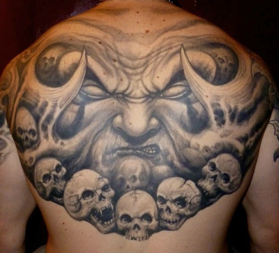 Gray washed style upper back tattoo of monster face wtih skulls