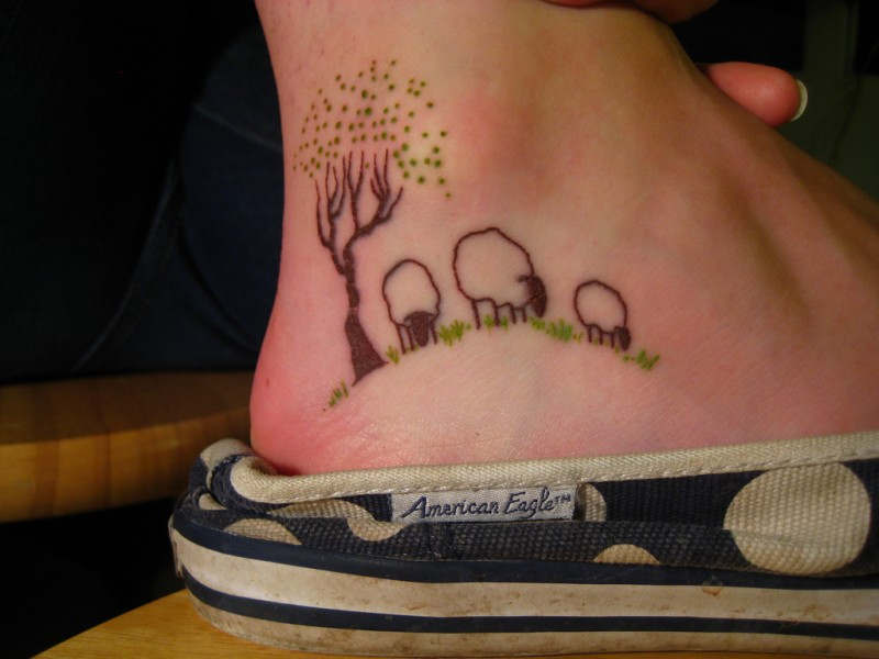 Grazing sheeps under tree tattoo on foot