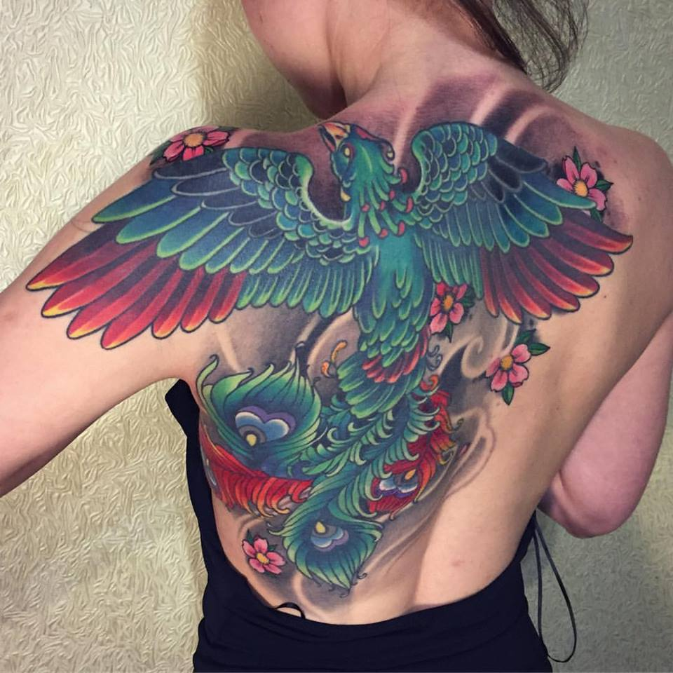 Great big fenix tattoo in green and red colors on upper back and shoulder