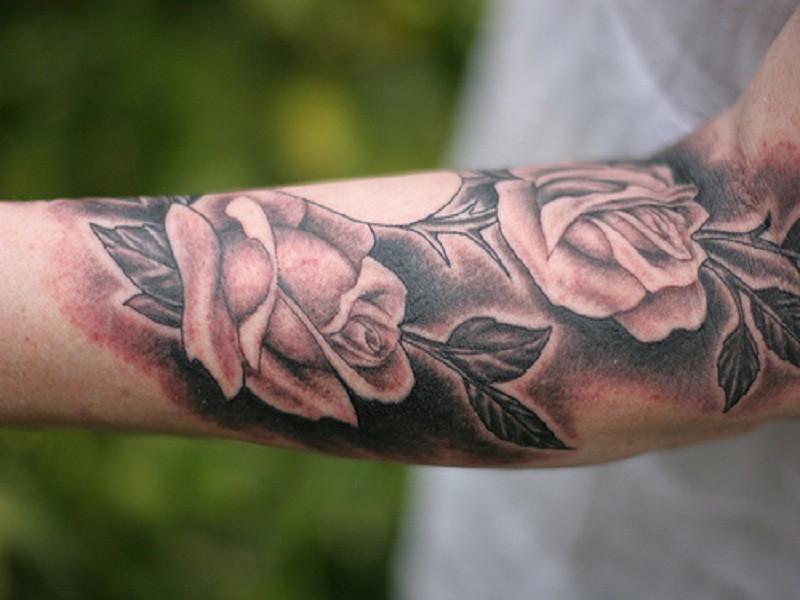 Tatuaje en el antebrazo, rosas con el fondo oscuro
