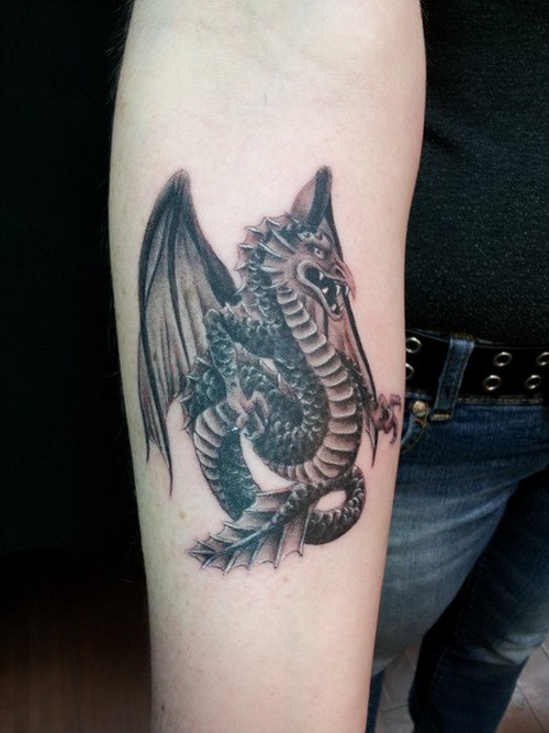 Great black-and-white winged dragon tattoo on forearm