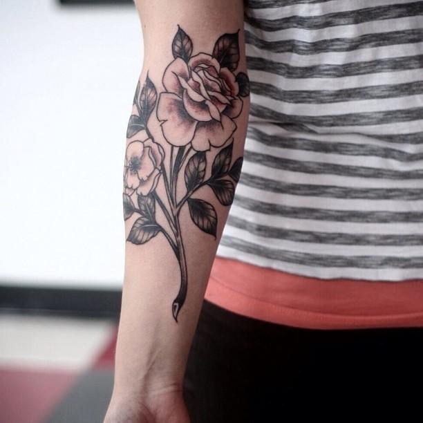Great black-ink vintage rose flower on stem tattoo on arm